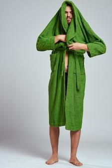 Emotionaler mann in einem grünen gewand auf einem hellen hintergrund