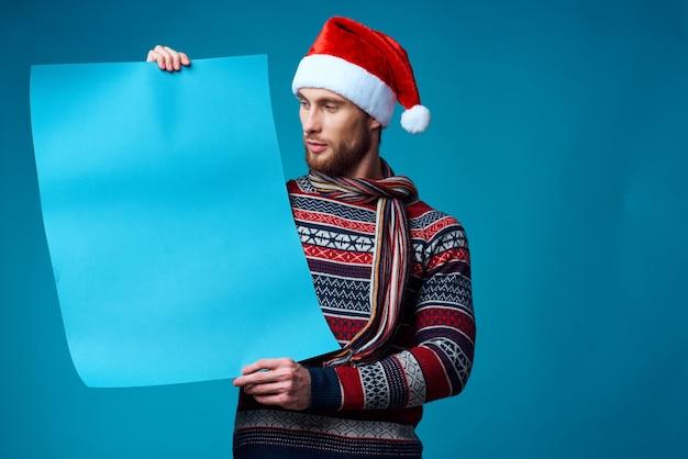 Emotionaler mann in einem weihnachtlichen blauen mockup-plakatstudio posiert
