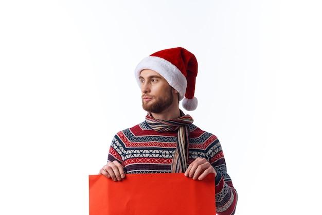 Emotionaler mann in einem weihnachtshut mit rotem modellplakat-kopierraumstudio