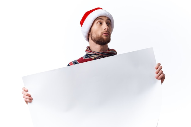 Emotionaler mann in einem weihnachtshut mit weißem mockup-plakat-weihnachtshintergrund