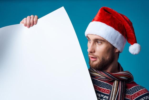 Emotionaler mann in einem weißen mockup weihnachten poster isolierten hintergrund. foto in hoher qualität