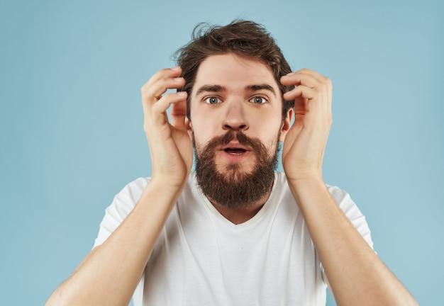 Emotionaler mann in einem weißen t-shirt ausdrucksstarken look studio. foto in hoher qualität