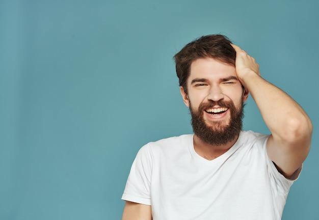 Emotionaler mann in einem weißen t-shirt ausdrucksstarker blick unzufriedenheit studio. foto in hoher qualität