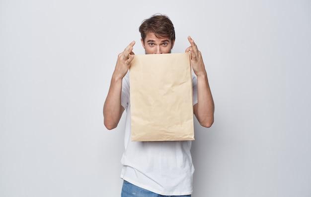 Emotionaler mann in einem weißen t-shirt mit einem bastelpaket in den händen des emotionsstudios isoliert