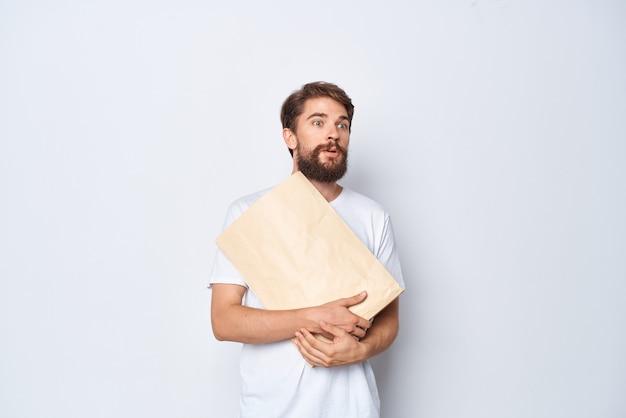 Emotionaler mann in einem weißen t-shirt mit einer papiertüte in den händen mocap-nahaufnahme