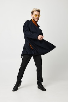 Emotionaler mann in modischer kleidung posiert auf hellem hintergrund und brille im gesicht. foto in hoher qualität