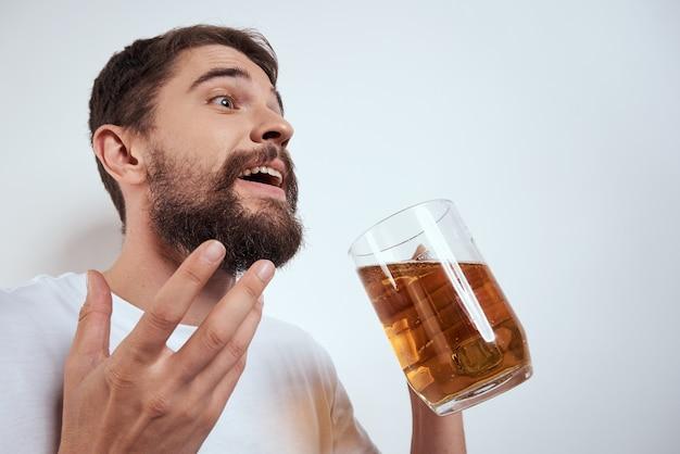 Emotionaler mann mit einem großen becher bier alkoholisches getränk gestikuliert mit seinen händen betrunken zustand. hochwertiges foto