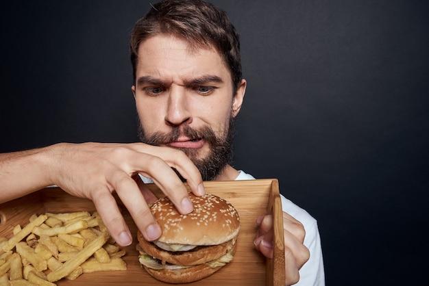 Emotionaler mann mit holzpaletten-fast-food-hamburger-pommes-frites, die den dunklen hintergrund des lebensmittellebensstils essen. hochwertiges foto
