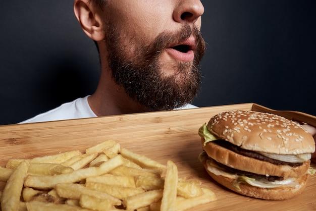 Emotionaler mann mit holzpaletten-fast-food-hamburger-pommes-frites, die lebensmittellebensstil essen