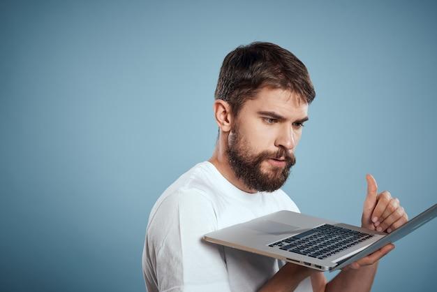 Emotionaler mann mit laptop in den händen auf blauem hintergrundmonitortastatur-internetmodell beschnittene ansicht. hochwertiges foto