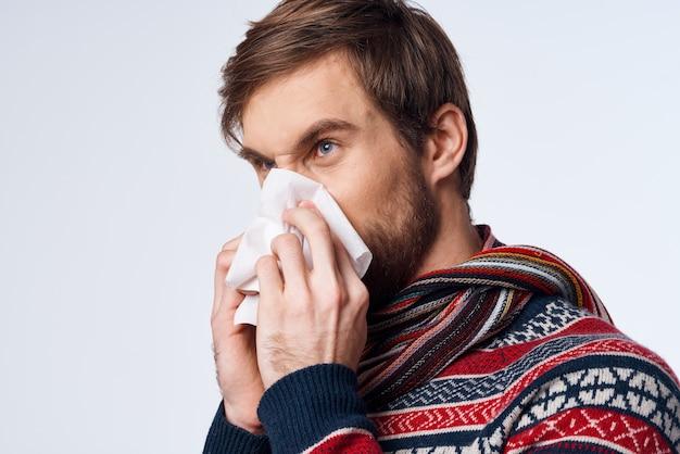 Emotionaler mann pullover gesundheitsprobleme taschentuch grippeinfektion isolierter hintergrund. foto in hoher qualität