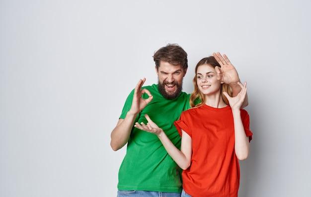 Emotionaler mann und frau im bunten t-shirt-familienlebensstilstudio.