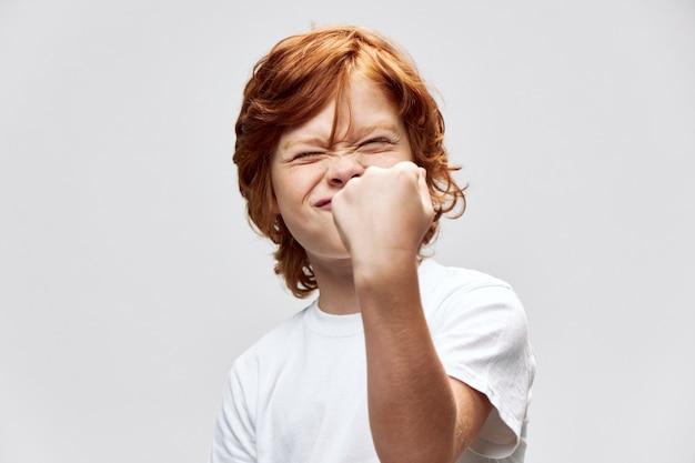Emotionaler modus ein junge mit zusammengekniffenen augen zeigt eine faust und ein gehorsames kind