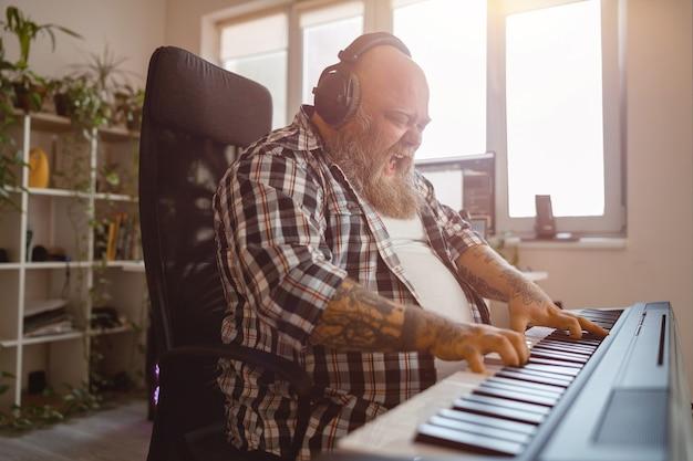 Emotionaler, plumper mann-komponist schreibt musik, die im studio einen sound-synthesizer spielt