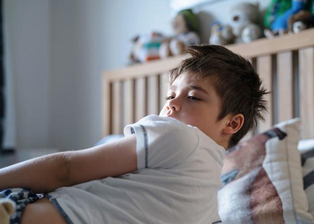 Emotionaler porträtjunge, der auf dem bett liegt, schläfriges kind, das morgens in seinem schlafzimmer mit morgenlicht aufwacht, kind 7 jahre alt, das sich im schlafzimmer entspannt. gesundheitsfürsorge für kinder oder schlafprobleme bei jungen kindern