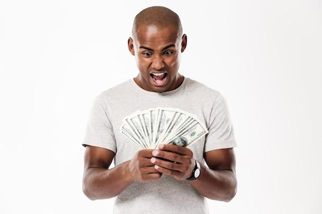 Emotionaler schreiender junger afrikanischer mann, der geld betrachtet.