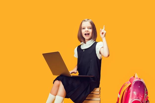 Emotionaler schüler sitzt hinter stapel büchern mit laptop hebt hand mit zeigefinger kindererziehung