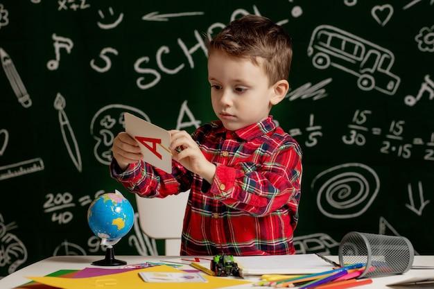 Emotionaler schuljunge, der mit vielen schulsachen auf dem schreibtisch sitzt. erster schultag. junge von der grundschule. zurück zur schule. kind von der grundschule.