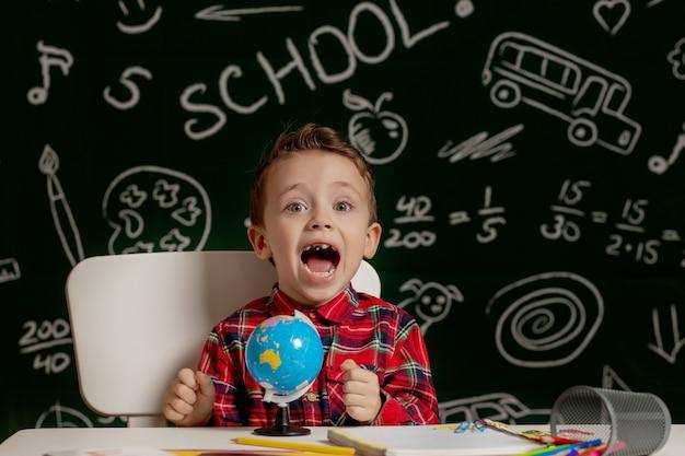 Emotionaler schuljunge, der mit vielen schulsachen auf dem schreibtisch sitzt. erster schultag. kind junge von der grundschule. zurück zur schule. kind von der grundschule.