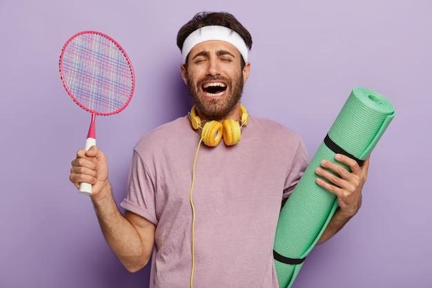 Emotionaler sportlicher mann trainiert mit fitnessmatte und tennisschläger, lacht mit überglücklichem gesichtsausdruck, hat dunkles haar, ist in freizeitkleidung gekleidet und hört während des trainings musik