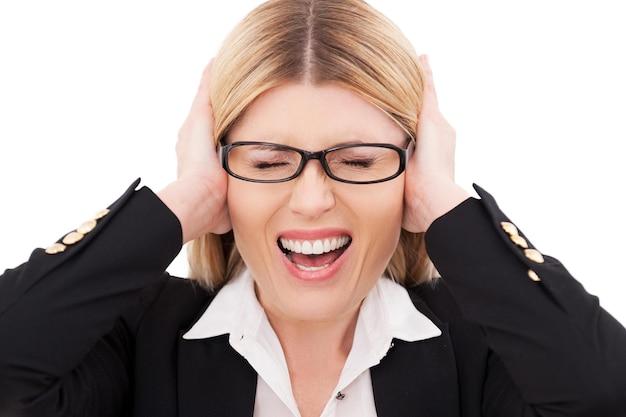 Emotionaler stress. depressive reife geschäftsfrau, die die augen geschlossen hält und die ohren mit den händen bedeckt, während sie isoliert auf weiß steht