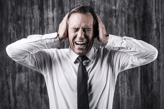 Emotionaler stress. gestresster reifer mann in hemd und krawatte, der den kopf in den händen hält und schreit, während er vor einer schmutzigen wand steht