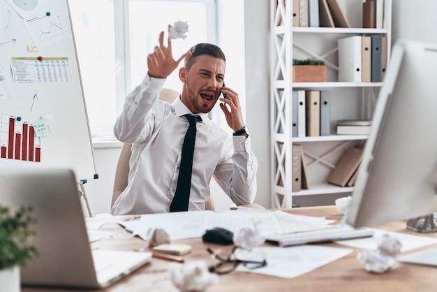 Emotionaler stress. müder junger mann in abendkleidung, der am telefon spricht und schreit, während er im büro sitzt sitting