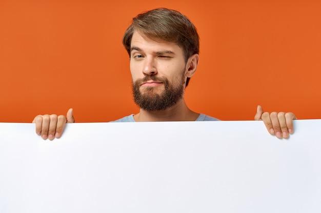 Emotionaler typ des plakatmodells, der ein weißes blatt papier hält. hochwertiges foto