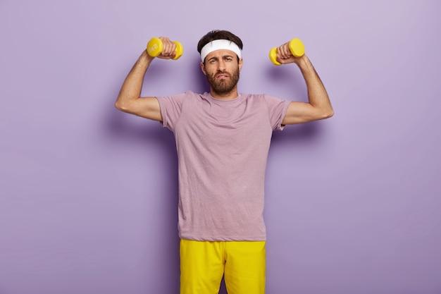Emotionaler unrasierter mann, der zum sport motiviert ist, einen gesunden lebensstil führt, starke muskeln haben möchte, gelbe hanteln hält, mit müde miene aussieht, in freizeitkleidung gekleidet