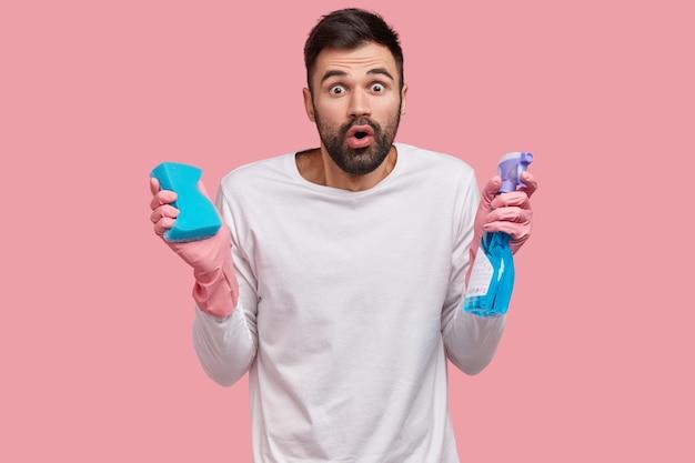 Emotionaler unrasierter mann mit verängstigtem gesichtsausdruck, hält eine flasche waschmittel und schwamm in der hand, erledigt die hausarbeit und ist am frühjahrsputz beteiligt