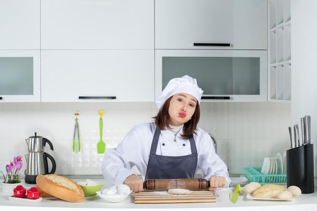 Emotionaler weiblicher commis-koch in uniform, der hinter dem tisch steht und gebäck in der weißen küche zubereitet