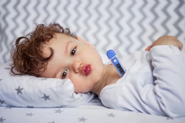Emotionales baby liegt in der krippe. körpertemperatur. thermometer unter dem arm. gesunder schlaf bei einer temperatur. einschlafen.