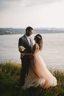 Emotionales bild des gerade verheirateten paares, das im feld steht und einander mit liebe ansieht. fluss im hintergrund.
