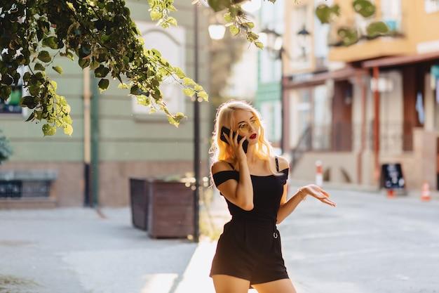 Emotionales blondes mädchen in der sonnenbrille mit telefon im sommersonnenschein