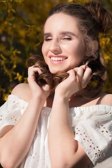 Emotionales brünettes mädchen mit schönem make-up, das in der nähe der blühenden gelben blumen posiert
