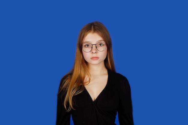 Emotionales dreizehnjähriges teenager-mädchen mit brille sieht sorgfältig, isoliert aus