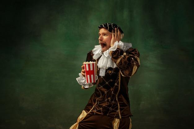 Emotionales fußball gucken. porträt des mittelalterlichen jungen mannes in der weinlesekleidung, die auf dunklem hintergrund steht. männliches modell als herzog, prinz, königliche person. konzept des vergleichs von epochen, moderne, mode.