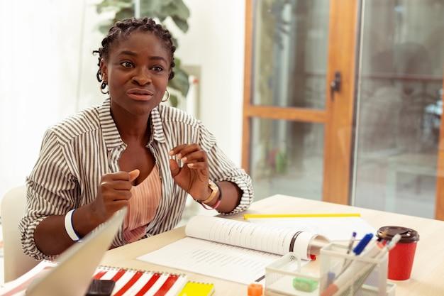 Emotionales gespräch. hübsche internationale weibliche person, die an ihrem arbeitsplatz sitzt, während sie neues material erklärt