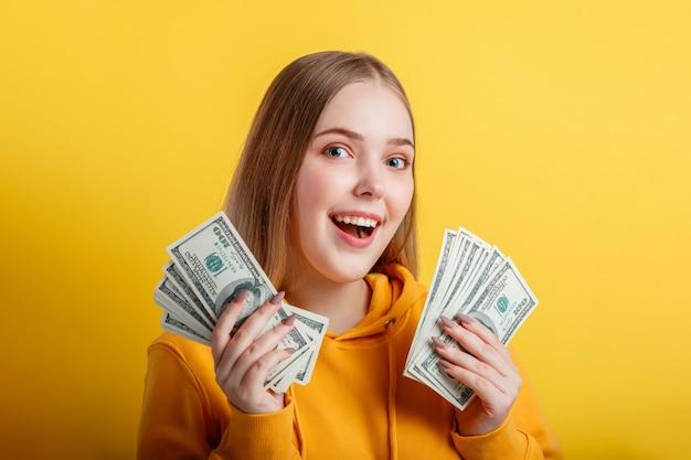 Emotionales glückliches blondes mädchen im teenageralter gewinnen geld bargeld, das dollar in den händen hält, die auf gelbem hintergrund der farbe lokalisiert werden. junge aufgeregte frau des porträts mit fan von geldbanknoten.