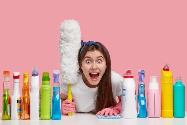 Emotionales hausmädchen schreit vor panik, sieht viel arbeit am haus und reinigt staub auf möbeln mit einer speziellen bürste, umgeben von reinigungsprodukten