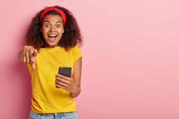 Emotionales junges mädchen mit dem lockigen haar, das im gelben t-shirt aufwirft