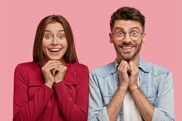 Emotionales junges paar, das gegen die rosa wand aufwirft