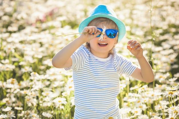 Emotionales kind im kamillenfeld. fröhliches kind mit blumen, die hut und sonnenbrille tragen. glücklicher junge in der sommerzeit draußen