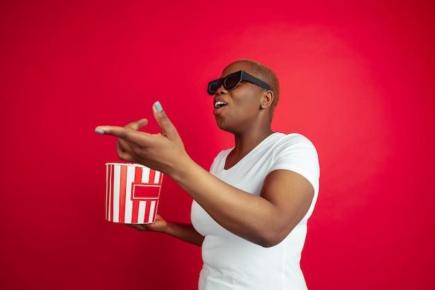 Emotionales kino gucken. porträt einer afroamerikanischen jungen frau auf rot