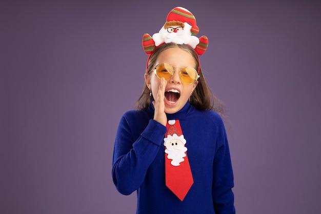 Emotionales kleines mädchen im blauen rollkragenpullover mit roter krawatte und lustigem weihnachtsrand auf dem kopf, der mit der hand in der nähe des mundes über der lila wand schreit