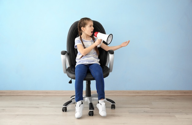 Emotionales kleines mädchen mit megaphon, das auf stuhl im leeren raum sitzt