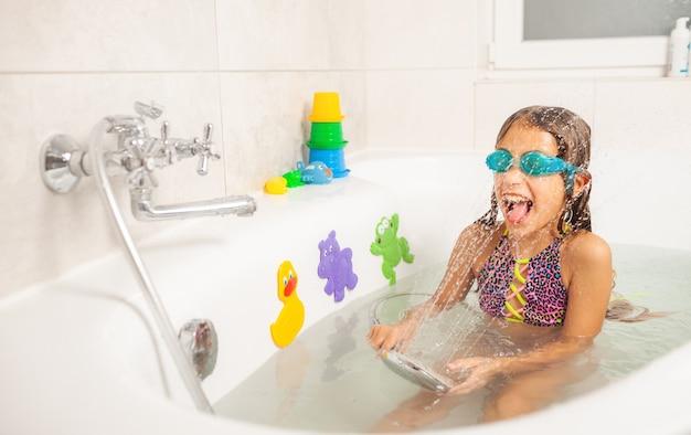 Emotionales lustiges kaukasisches mädchen spielt freudig mit wasser beim baden im badezimmer. konzept der unterhaltung und hygiene gesunder kinder. exemplar