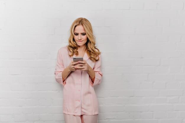 Emotionales mädchen im baumwollpyjama, das mit telefon auf weißer wand aufwirft. schöne lockige frau im rosa nachtanzug, der smartphonebildschirm betrachtet.