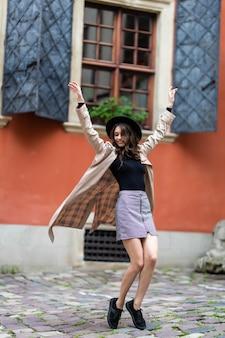 Emotionales mädchen im trendigen schwarzen hut, der auf stadt springt. blithesome europäisches weibliches modell, das im mantel aufwirft.