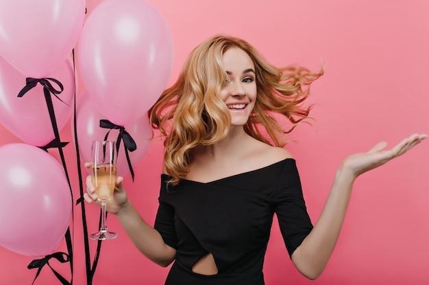 Emotionales mädchen mit blondem lockigem haar, das an ihrer geburtstagsfeier mit weinglas tanzt. prächtiges junges weibliches modell in der schwarzen kleidung, die mit rosa luftballons aufwirft.